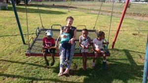 Mella und die Kids sitzen auf der Schaukel.